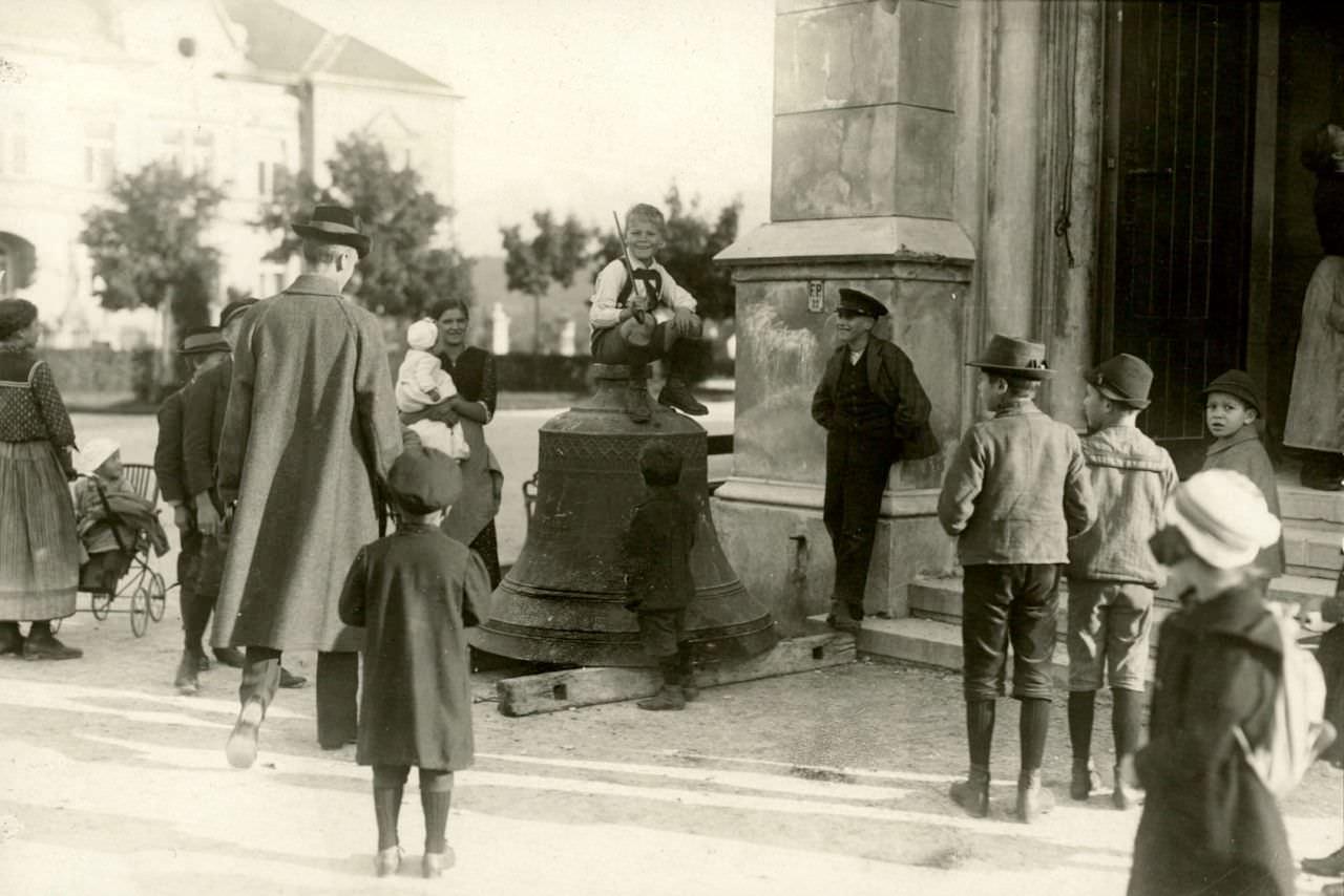 Kinder auf einer der abgenommenen Glocken der evangelischen Kirche im Stadtpark Villach im September 1916