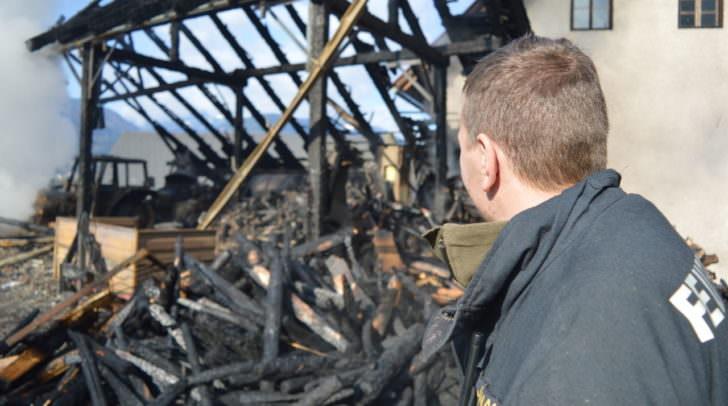 Ein Freiwilliger Feuerwehrmann vor dem zerstörten Wirtschaftsgebäude in Saak