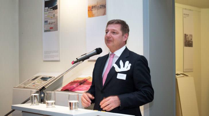 Bürgermeister Günther Albel bei der Eröffnung der Ausstellung in der Villa Dessauer in Bamberg. Der Baumwollhandschau – statt eines Stecktuches – symbolisiert, wie die Gäste in den Künstlerbüchern blättern können.