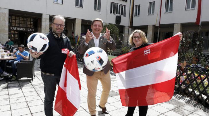 Alle Zeichen stehen auf Fußball: Bürgermeister Günther Albel (Mitte), Krone-Chefredakteur Hannes Mösslacher und Rathauscafé-Wirtin Valentina Tosoni fiebern dem großen Fußballfest mit dem Public Viewing auf dem Villacher Rathausplatz entgegen.
