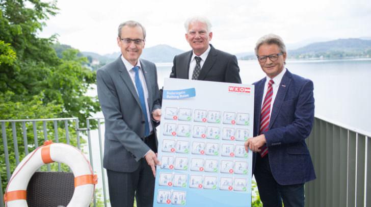 Gerhard Baumgartner, Christian Ochsenbaum und Valentin Happe mit den neuen Piktogrammen für Kärntens Bäder.