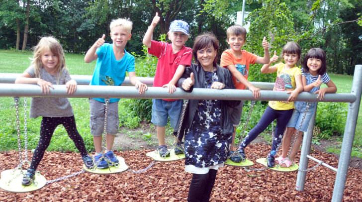 """Kindergartenreferentin Vizebürgermeisterin Petra Oberrauner freut sich mit den Kleinen vom Kindergarten """"Tratten"""" über die neuen Spielgeräte am Wasenboden."""