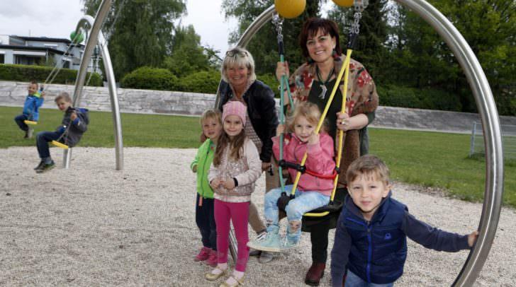 Vizebürgermeisterin Petra Oberrauner und Kindergartenleiterin Brigitte Kotschnig testen gemeinsam mit Kindern des Kindergartens Tratten die neuen Schaukeln beim Kinderland am Wasenboden.