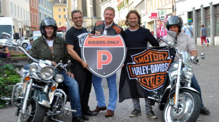 Tourismusverband-Obmann Dr. Martin Domenig, Bürgermeister Günther Albel und Hubert Marko, stellvertretender Aufsichtsratsvorsitzender des Stadtmarketings mit Harley-Gästen auf dem Villacher Hauptplatz.