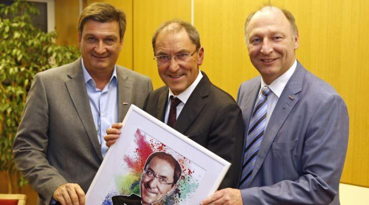WK-Präsident Jürgen Mandl und WK-Spartenobmann Martin Zandonella gratulierten Volkmar Fussi – hier mit seinem kreativen Ebenbild - zum Kommerzialratstitel