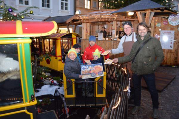 Die Kids können sich im Vorbeifahren die süßen Waffeln holen: Am Bild Ingolf Hanschur und Hubert Marko (Stellvertretender Aufsichtsratsvorsitzender des Stadtmarketings) mit den begeisterten Kindern.