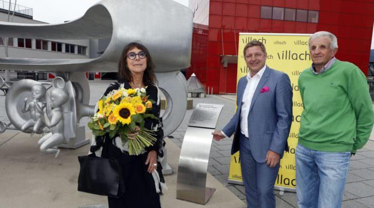 """Gironcoli-Witwe Christine Gironcoli, Bürgermeister Günther Albel und Kunstmäzen Wolfgang Gabriel vor jener Skulptur, die dem Förderpreis für junge Künstlerinnen und Künstler den Namen gibt: """"Wir Villacher Kinder"""" (vor dem CCV)."""