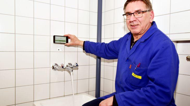Moderne Legionellen-Prophylaxe: Schulwart Peter Warmuth spült in der Friedensschule mit Unterstützung von Smnartphone und QR-Code