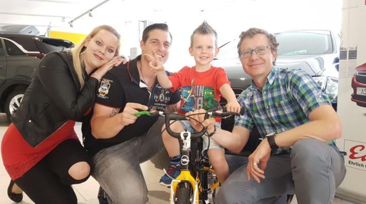 Die Gewinnerfamilie mit Opelverkaufsberater Gernot Netzer bei der Fahrradübergabe