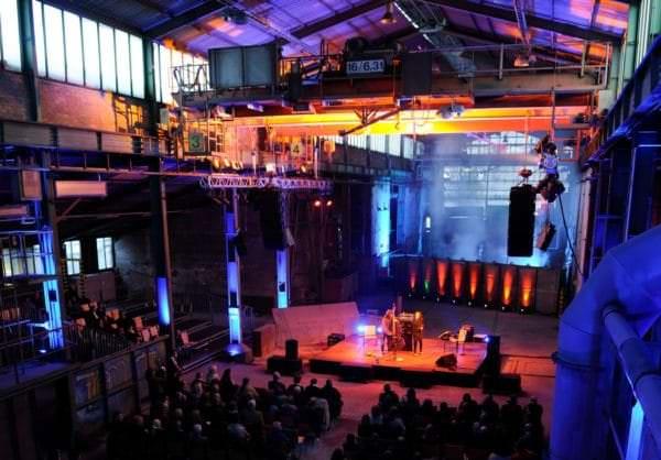 Das Konzert findet in einer historischen Werkshalle statt.
