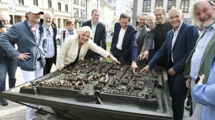 Bürgermeisterin Dr. Maria-Luise Mathiaschitz freut sich mit ihren Senatskollegen, der hohen Geistlichkeit, Restaurator Marco Tomasi und Kunstschmied Markus Pirker (ganz links) über das hochwertige Relief und zeigt den Modell-Standort auf dem Domplatz.