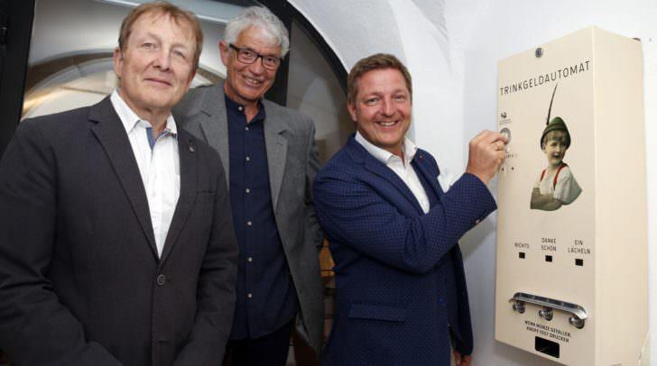 """Bürgermeister Günther Albel, Werner Koroschitz und Kurt Karpf, hier am Kunstobjekt """"Trinkgeldautomat"""", freuen sich über das große Interesse an der gelungenen Ausstellung """"Zimmer frei""""."""
