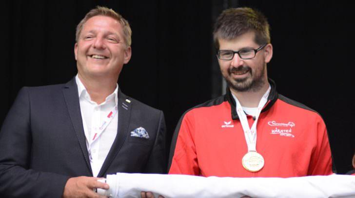 Villachs Bürgermeister Günther Albel und Mario Horn von der Diakonie de la Tour Treffen mit der eingerollten und übergebenen Special Olympics Fahne