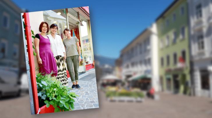"""Das Weltladenteam Hildegard Ronacher und Renate Kuttnig präsentieren Vizebürgermeisterin Dr.in Petra Oberrauner ihren """"grünen"""" Ladeneingang."""