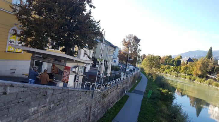 Der Bratwurstkönig an der Villacher Draubrücke – auch die Aussicht passt.