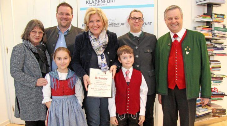 Neues Ehrenmitglied bei der Kindervolkstanzgruppe Klagenfurt ist Bürgermeisterin Dr. Maria-Luise Mathiaschitz, die die Urkunde von Helmut Palko im Beisein von Günther Palko, Sylvia Oberwinkler, den jungen Tänzern Martina und Clemens sowie Protokollchefin Mag. Eva Janica überreicht bekam.
