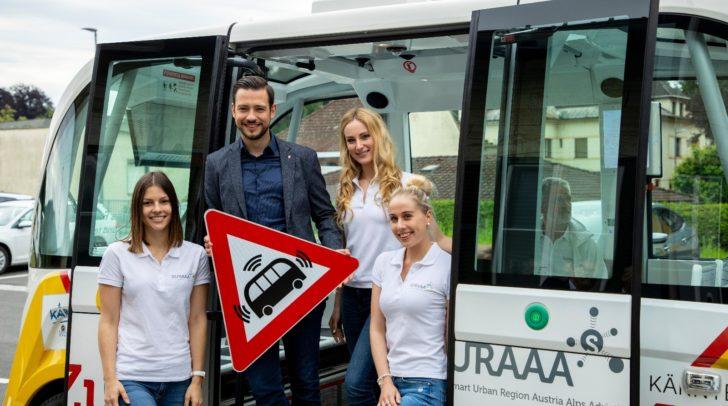 """Kärntens """"autonomes Bus-Shuttle"""" ist seit gestern wieder in Pörtschach unterwegs. Am Bild: LR Sebastian Schuchnig mit Mitarbeiterinnen des autonomen Shuttles."""
