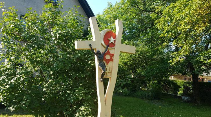 Die Symbole auf der Skulptur stehen für das Christentum, das Judentum, den Islam und den Hinduismus.