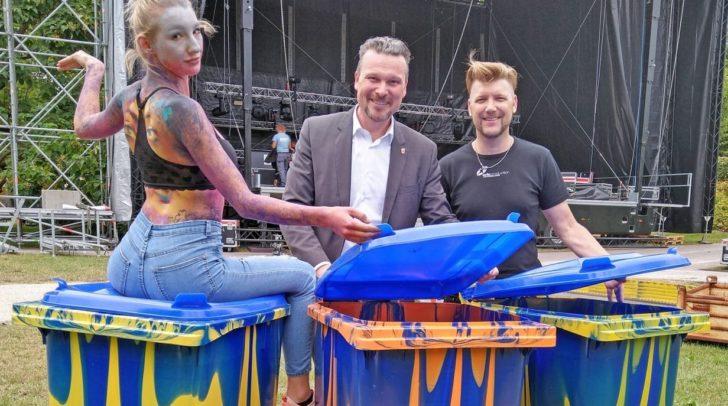 Bunte Körper und bunte Tonne: Vizebürgermeister Wolfgang Germ mit Alex Barendregt und einem Modell auf einer bunten Mülltonne.