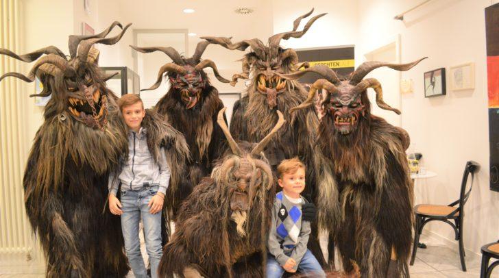 Die Brauchtumsgruppe Techelsberg zu Besuch im Stadtmarketing: Fynn und Luis freuen sich inmitten der schaurigen Gesellen schon auf den Krampusumzug.