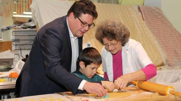 Marktreferent Stadtrat Christian Pober und ein kleiner Bäcker ließen sich von Marlene Wiedergut zeigen, wie man schöne Kekse aussticht.