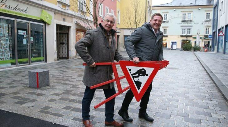 Bürgermeister Günther Albel und Stadtrat Harald Sobe entfernen symbolisch das letzte Straßenschild an der Draulände.