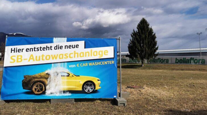 Ein Plakat kündigt den Neubau der SB Autowaschanlage an.