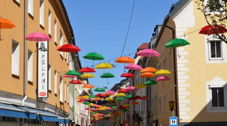 Ein Meer von magisch schwebendenSchirmen taucht die Altstadt-Gasse in eine schöne, farbenfroheSzenerie