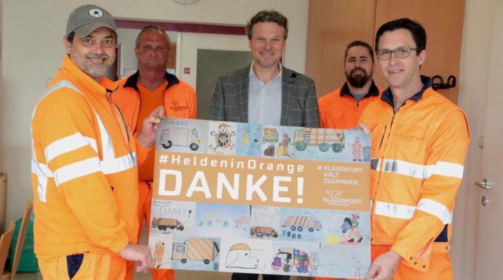 """Entsorgungsreferent Vzbgm. Wolfgang Germ und Mitarbeiter der Entsorgung präsentieren die besten Kinderzeichnungen der Aktion """"Helden in Orange""""."""