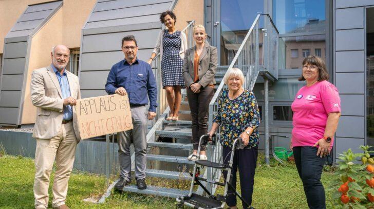 Die Pflege darf nicht zum Pflegefall werden: Caritasdirektor Sandriesser (2.v. li.) mit Bewohnerin Anna Strieder, Pflegefachkraft Christine Sadnek und den Bereichsleiter*innen Rössler-Merlin (4. v. li), Wernig und Hude (links).