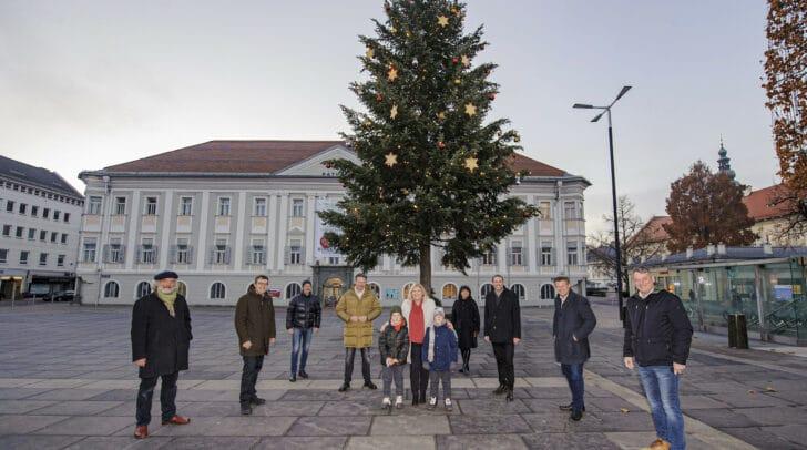 Vertreter des Stadtsenates und des Gemeinderates vor dem beleuchteten Christbaum am Neuen Platz. Neben der Bürgermeisterin stehen die beiden Kinder Leopold und Taddäus.
