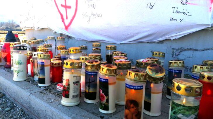 Kerzen und kleine Andenken stehen am Unfallort unter einem großen Plakat.
