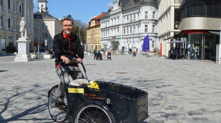 City-Bote Georg Moser ist mit seinem Elektro-Lastenfahrrad wieder in der Villacher Innenstadt unterwegs und bringt die schweren Einkaufstaschen der Innenstadtkunden zum Parkplatz oder auch nach Hause.