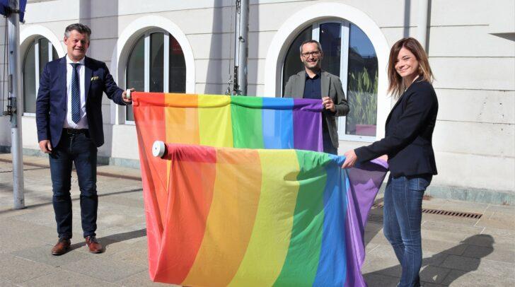Bürgermeister Christian Scheider hisst gemeinsam mit Stadträtin Mag.a Corinna Smrecnik und Stadtrat Mag. Franz Petritz die Regenbogenfahne vor dem Rathaus.