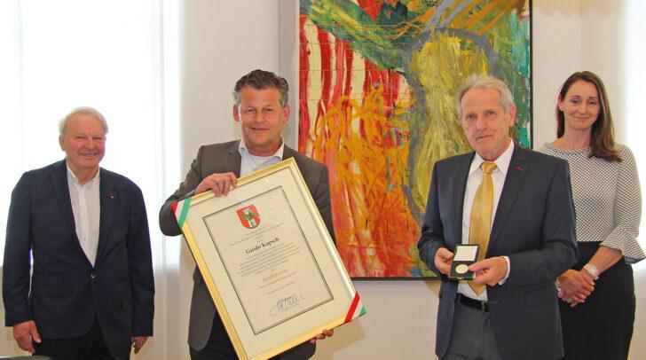 Goldschmiedemeister Guido Kapsch erhält im Beisein seiner Tochter Dr. Karoline Kirchhammer und Mag. Erich Wappis den Ehrpfennig der Landeshauptstadt Klagenfurt von Bürgermeister Christian Scheider.